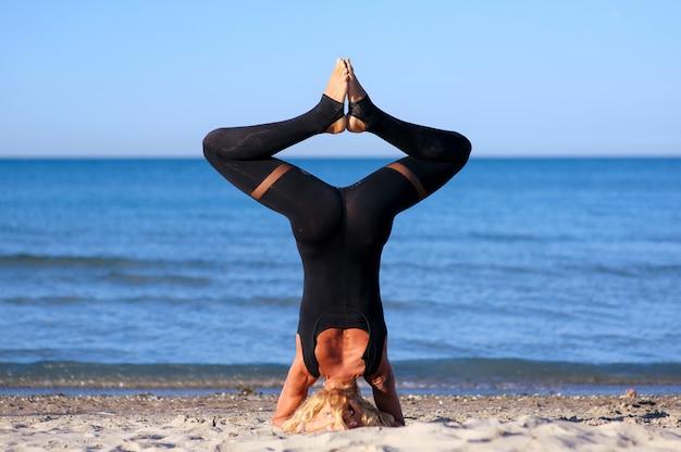 Frau, die yoga asana am strand tut Premium Fotos
