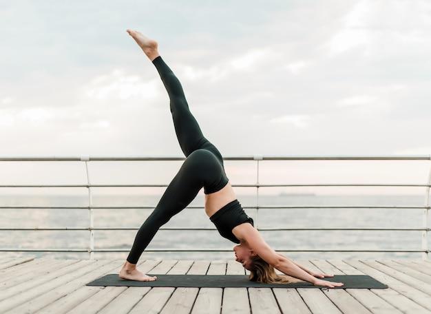 Frau, die yoga auf dem strand in schwieriger asana position tut Premium Fotos