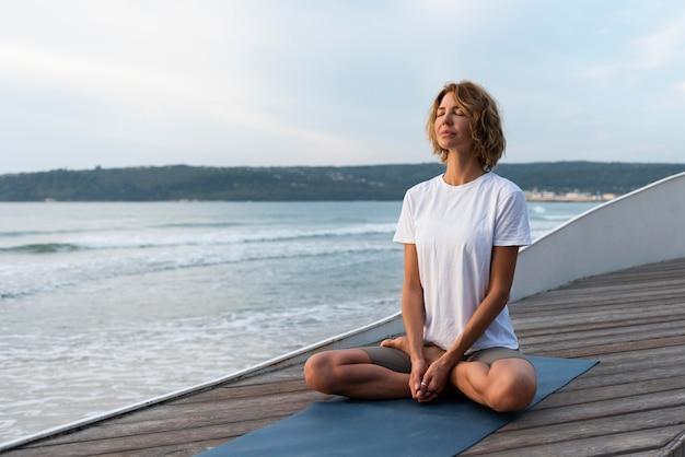Frau, die yoga-haltung nahe meer praktiziert Kostenlose Fotos