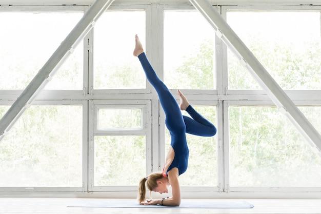 Frau, die yoga oder pilates übung und handstandhaltung tut. Premium Fotos
