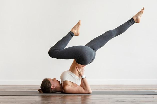 Frau, die yoga-positionen auf matte zu hause ausübt Kostenlose Fotos