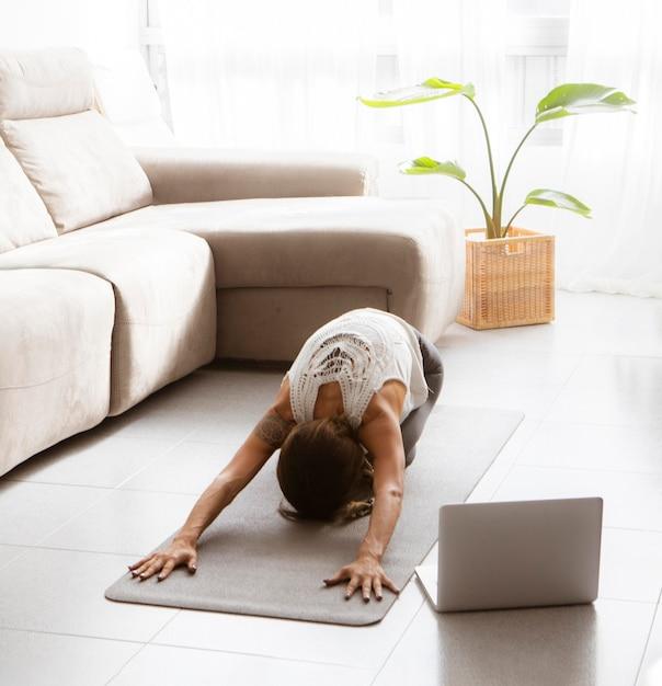Frau, die yoga zu hause auf matte mit laptop auf dem boden tut Kostenlose Fotos