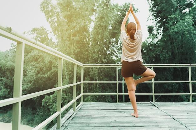 Frau, die yogaübung am morgen mit natürlichem hintergrund tut. Premium Fotos