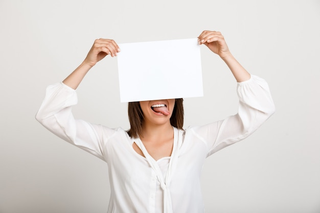 Frau, die zeichen auf weißem papier zeigt, machen ankündigung Kostenlose Fotos