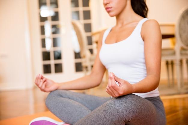 Frau, die zu hause auf boden zu hause tut, meditation zu tun Premium Fotos