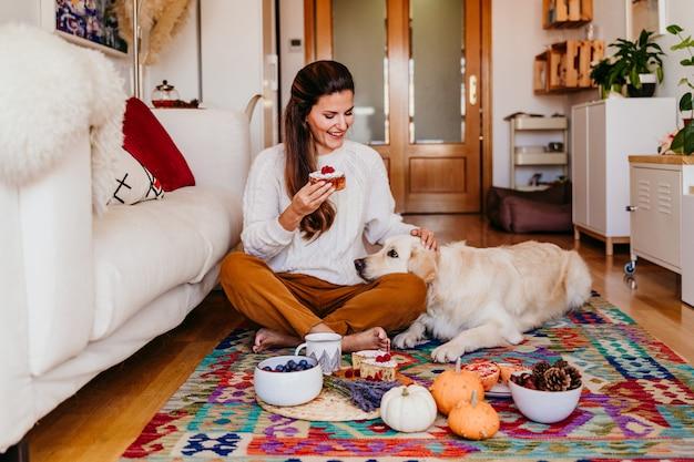 Frau, die zu hause ein stück bonbon während des frühstücks hält. Premium Fotos