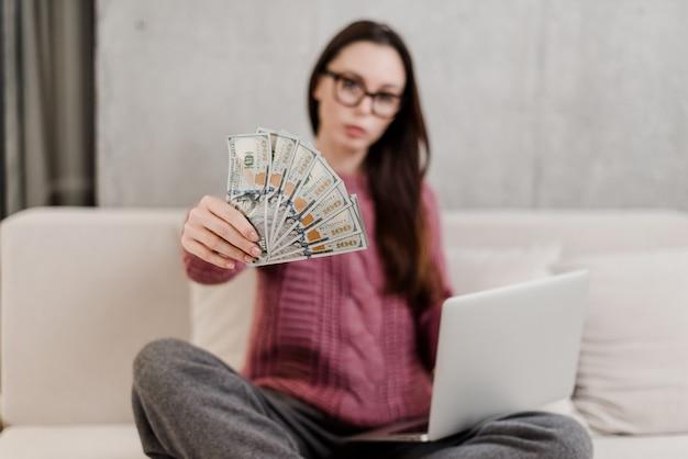 Frau, die zu hause geld auf einer couch mit laptop verdient Premium Fotos