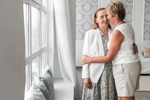 Frau, die zu hause ihre ältere mutter küsst Kostenlose Fotos
