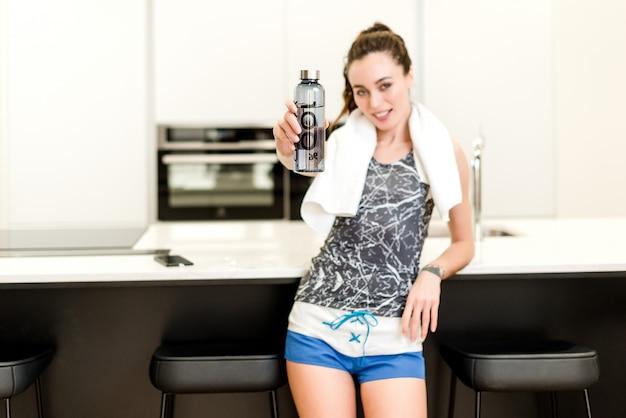 Frau, die zu hause training und trinkwasser von der flasche tut Premium Fotos