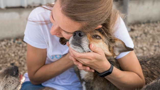 Frau, die zuneigung zeigt, um hund im tierheim zu retten Premium Fotos