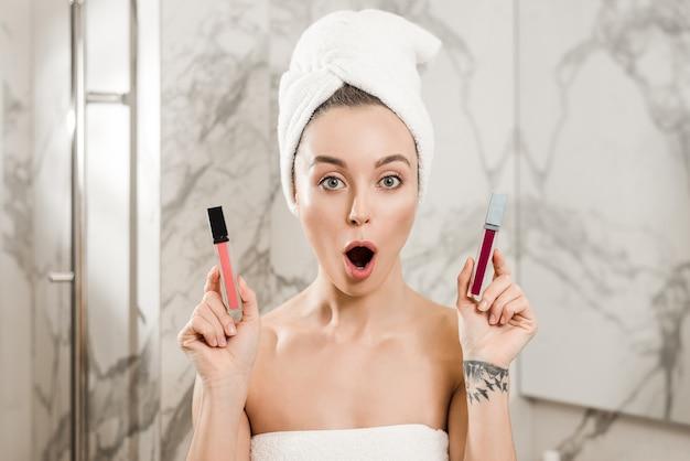 Frau, die zwischen den lippenstiften tun make-up im badezimmer nach dusche wählt Premium Fotos