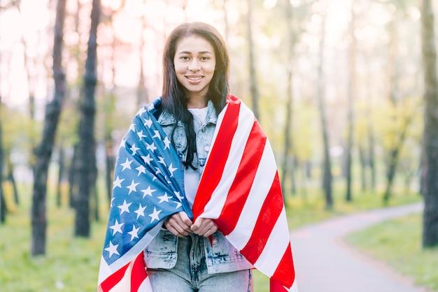 Frau draußen eingewickelt in der amerikanischen flagge Kostenlose Fotos
