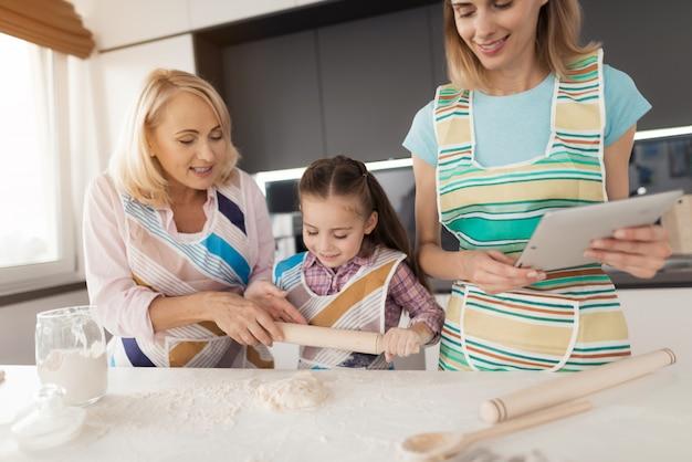 Frau, ein mädchen und eine frau mittleren alters kochen einen kuchen Premium Fotos