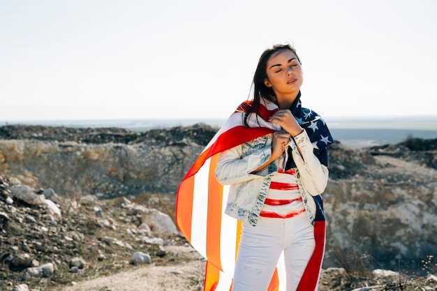 Frau eingewickelt in der markierungsfahne, die auf berg steht Kostenlose Fotos