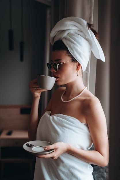 Frau eingewickelt in einem tuch nach einem trinkenden kaffee der dusche Kostenlose Fotos