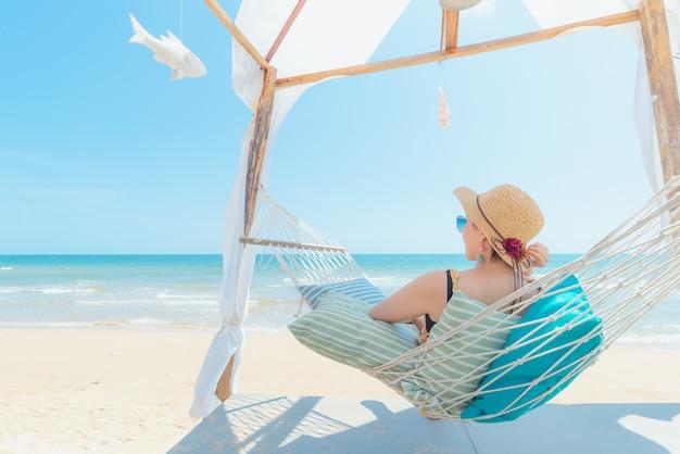 Frau entspannend in der hängematte am strand Premium Fotos