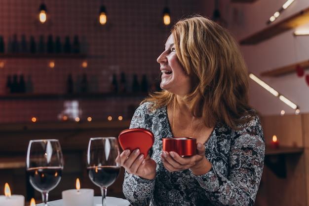 Frau freut sich, einen kasten mit einem geschenk zum valentinstag in einem restaurant zu öffnen Premium Fotos