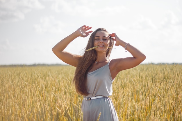 Frau gebräunte haut lange braune haare silber seidenkleid stehend auf einem feld Premium Fotos