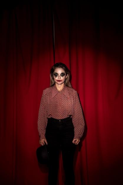 Frau gekleidet als clown, der in der front auf einem vorhang steht Kostenlose Fotos