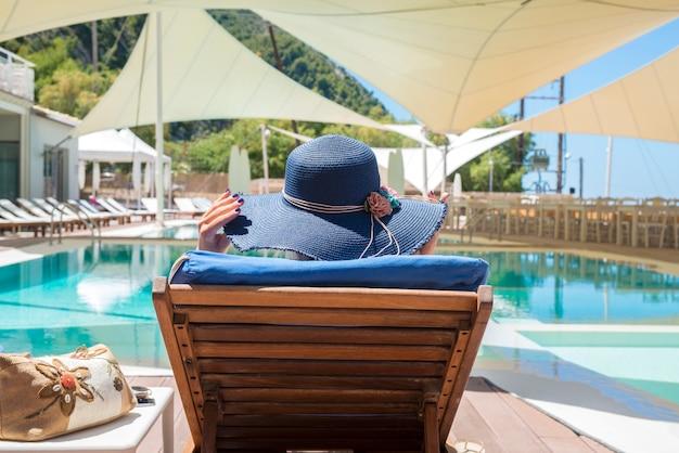 Frau genießt und entspannt auf liegestuhl am pool Kostenlose Fotos