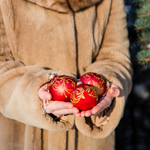 Frau getragen im pelzmantel, der in seinen händen die nahaufnahme mit drei rote weihnachtsbällen hält Premium Fotos