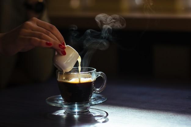 Frau gießt milch in ihren kaffee Kostenlose Fotos