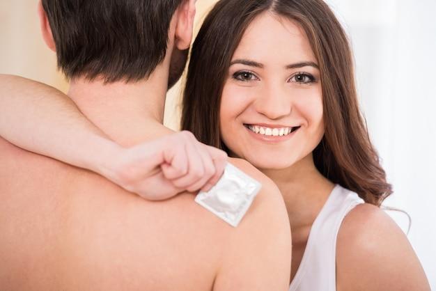 Frau hält ein kondom und ein lächeln. Premium Fotos