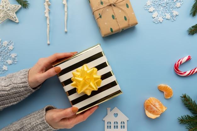 Frau hält ein weihnachtsgeschenk in ihren händen Premium Fotos