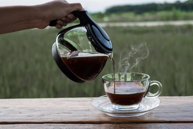 Frau hält eine kaffeekanne und lässt sich auf das glas auf dem holztisch fallen Premium Fotos