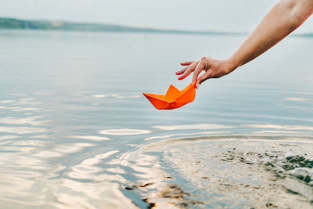 Frau hält im sommer ein papierboot an den fingern über dem fluss. Premium Fotos