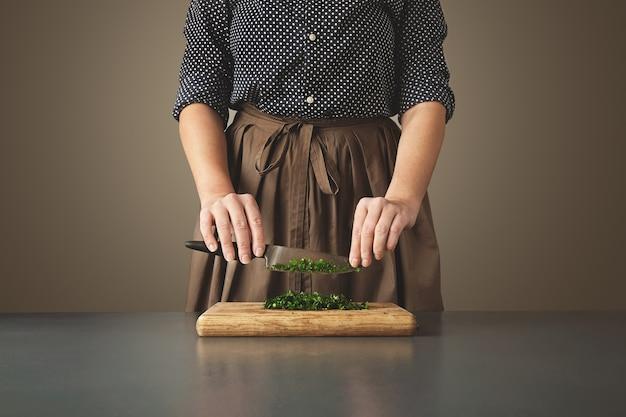 Frau hält messer über gehackter grüner petersilie auf holzbrett auf gealtertem blauem tisch. nicht erkennbare hausfrau Kostenlose Fotos