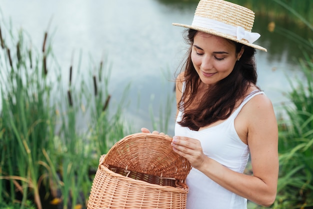 Frau hält picknickkorb am see Kostenlose Fotos