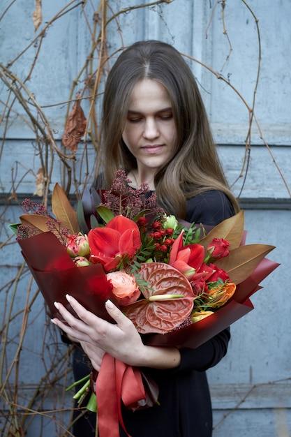 Frau hält schicke herbst bouquet in roten farben im vintage-stil im freien Premium Fotos