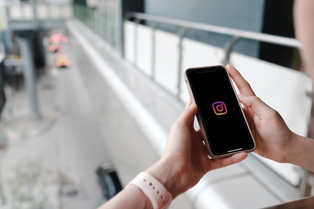 Frau hält smartphone mit sozialen medien auf dem bildschirm Premium Fotos