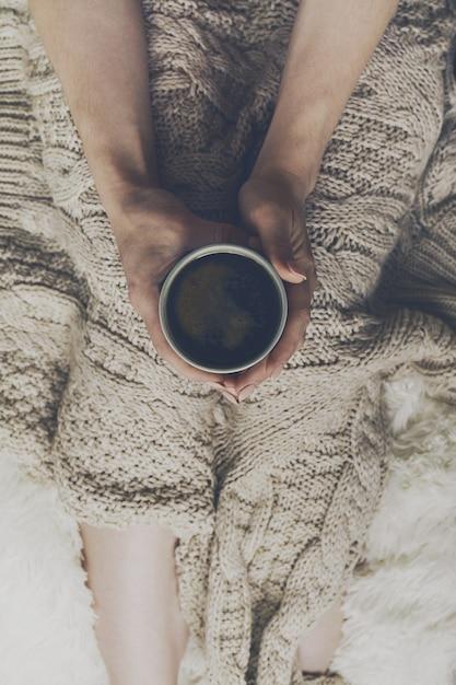 Frau hände halten leckeren warmen kaffee espresso in keramik tasse sitzen auf bett mit plaid. home-konzept. draufsicht. Kostenlose Fotos