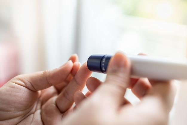 Frau hände mit lanzette am finger, um diabetes blutzuckerspiegel von glukose-meter am morgen zu überprüfen. Premium Fotos