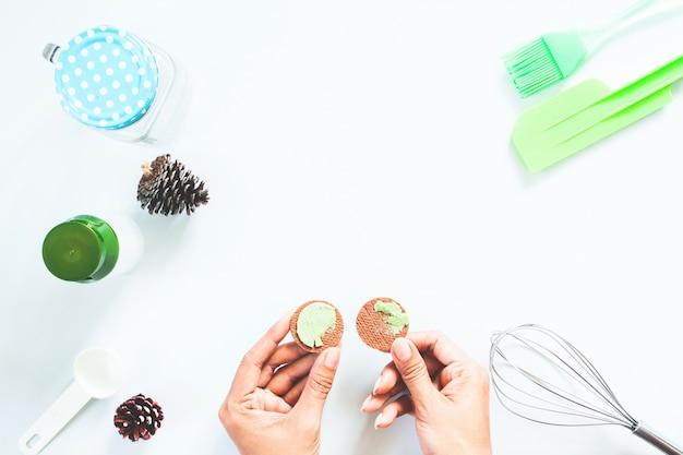 Frau hände mit macha grüner tee sahne cookie und bäckerei werkzeuge auf weißen tisch, flat lay Kostenlose Fotos