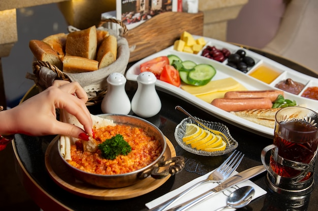 Frau hand eintauchen brot auf ei und tomatenteller zum frühstück setup serviert Kostenlose Fotos