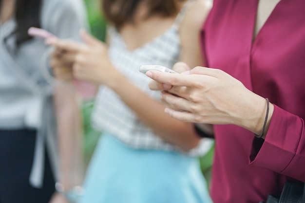 Frau hand halten smartphone-gerät für die arbeit und anwendung mit freunden spielen Premium Fotos