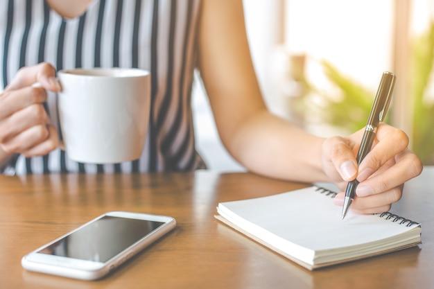 Frau hand schreibt auf einen notizblock mit einem stift. Premium Fotos