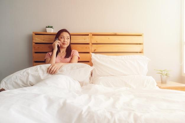 Frau hat ein telefongespräch auf ihrem bett morgens. Premium Fotos