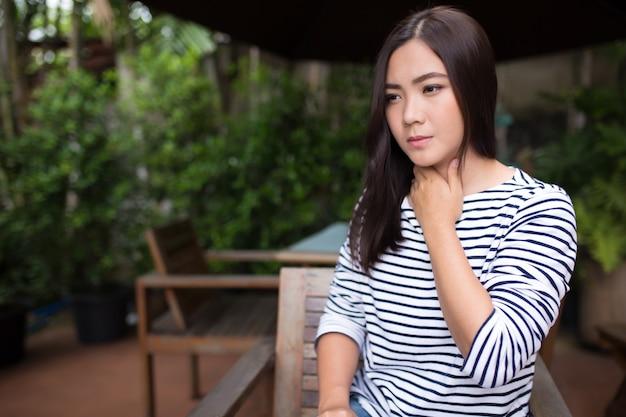 Frau hat halsschmerzen im café Premium Fotos