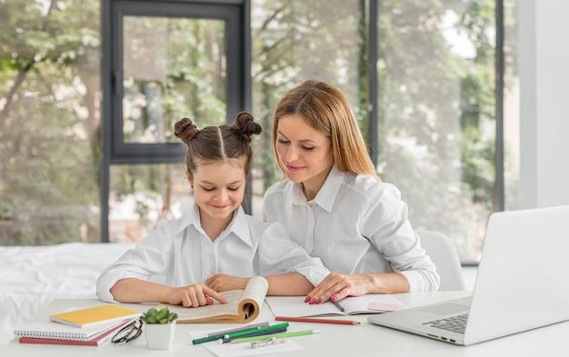 Frau hilft ihrem schüler mit ihren hausaufgaben Kostenlose Fotos