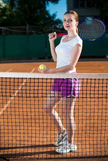 Frau hinter einem netz, das den tennisball hält Kostenlose Fotos