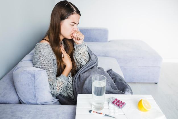 Frau hustet auf der couch Kostenlose Fotos