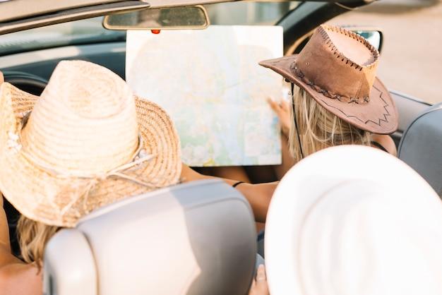 Frau im auto, das karte betrachtet Kostenlose Fotos