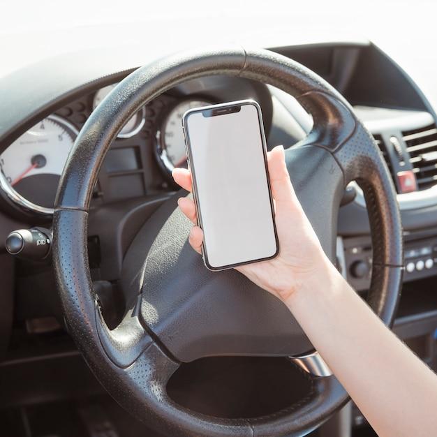 Frau im auto, das smartphoneschablone betrachtet Kostenlose Fotos
