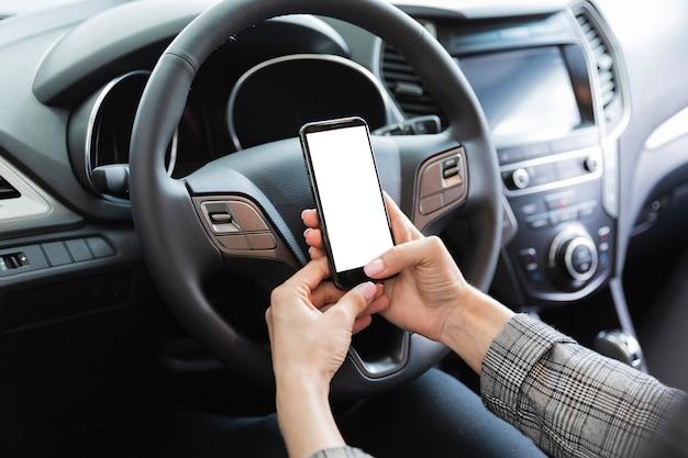 Frau im auto, das telefonmodell hält Kostenlose Fotos