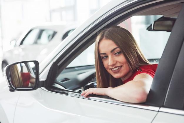 Frau im auto drinnen hält rad umdrehend lächelnd und betrachtet passagiere auf dem rücksitz idee taxifahrer gegen sonnenuntergangsstrahlen lichtscheinhimmel konzept der prüfung fahrzeug - zweites zuhause das mädchen Premium Fotos