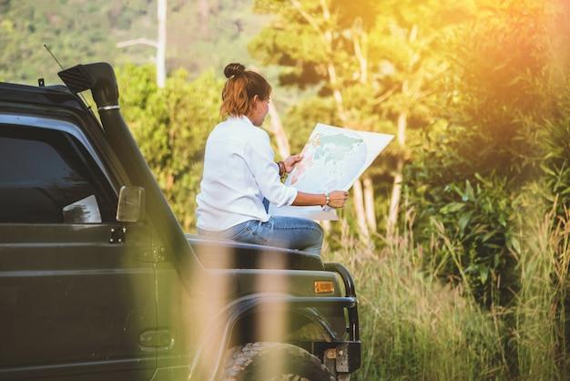 Frau im auto durch reise mit einer karte Premium Fotos